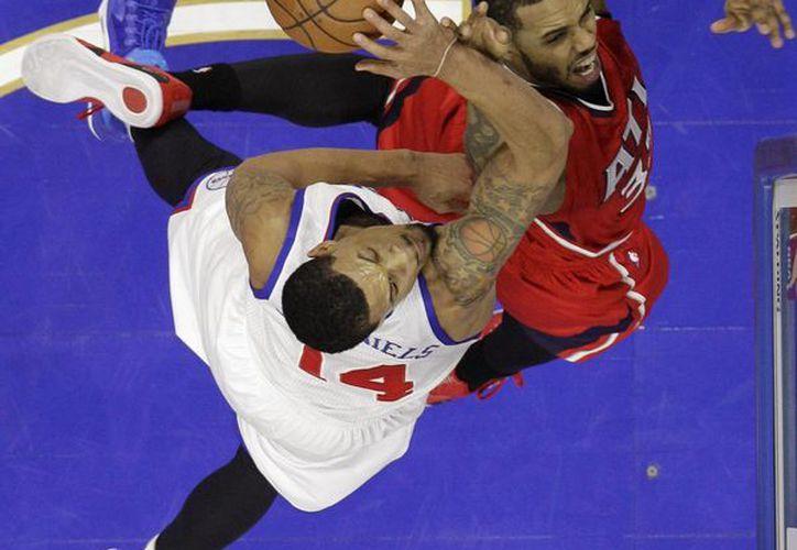 K.J. McDaniels, de los 76ers, bloquea un disparo de Mike Scott, de Hawks, en la segunda mitad del partido de la NBA. (Foto: AP)