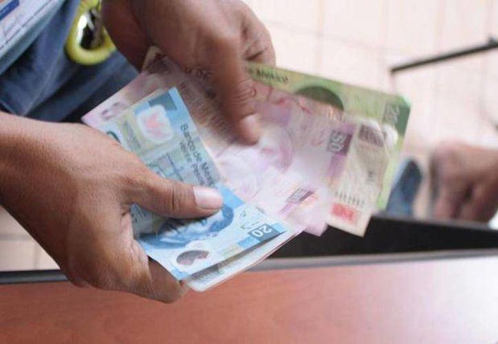 Desde octubre de este año sólo existe en el país  un salario mínimo general: 70.10 pesos por día. Imagen de una persona mientras cuenta unos billetes. (Archivo/SIPSE)