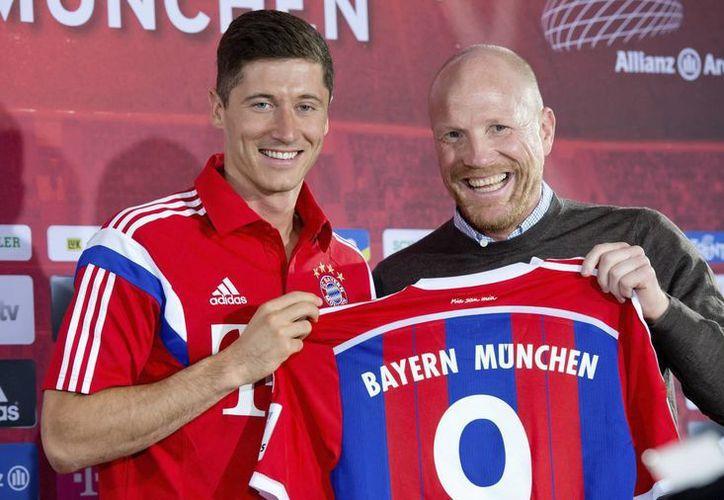 El delantero polaco Robert Lewandowski (i) posa junto al director deportivo del Bayern Múnich, Matthias Sammer, durante su presentación en Múnich. (EFE)