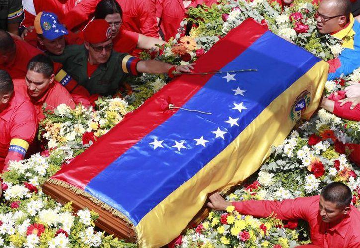 Un miembro de la guardia presidencial superior coloca una flor sobre el ataúd que contiene el cuerpo de Venezuela, Hugo Chávez. (Agencias)