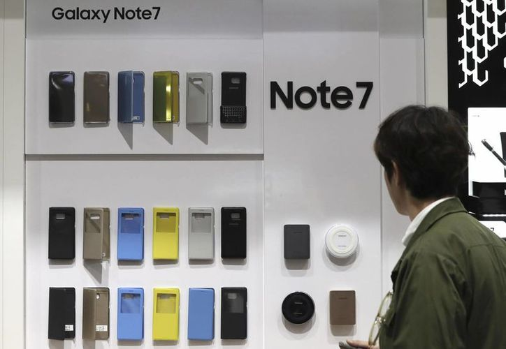 Un visitante observa varios gabinetes de teléfonos celulares Galaxy Note 7 de Samsung Electronics en una tienda en Seúl, Corea del Sur. Samsung prevé un aumento de sus ganancias mayor al pronosticado para el trimestre julio-septiembre a pesar de haber dispuesto un retiro sin precedentes de sus teléfonos celulares más distintivos de la marca. (AP Foto/Lee Jin-man)