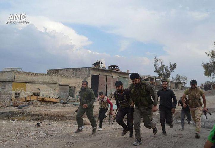 Combatientes del Ejército Libre Sirio corren hacia una de las líneas del frente en un poblado de Alepo, Siria. (Agencias)