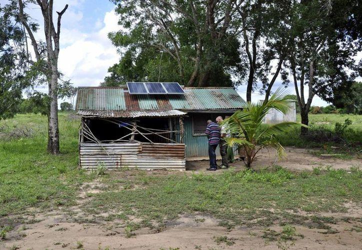 El director de proyectos en Kenia de la empresa española BDT, Roberto González, comprueba junto al responsable (playera rayada), los datos del panel solar instalado sobre un dispensario médico en Hindi. (EFE)