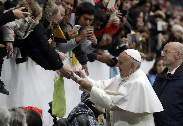El Papa Francisco firma un libro mientras saluda a los fieles a su arribo al estadio de Malmo, Suecia. (AP/Andrew Medichini)