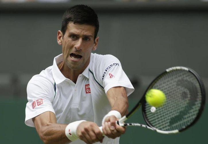 Novak Djokovic(foto) es el actual campeón del abierto de Wimbledon, busca conseguir otro título que lo mantenga en la punta de la clasificación de la ATP. En la foto; Novak consigue un buen contacto durante uno de los sets del partido de hoy. (AP)