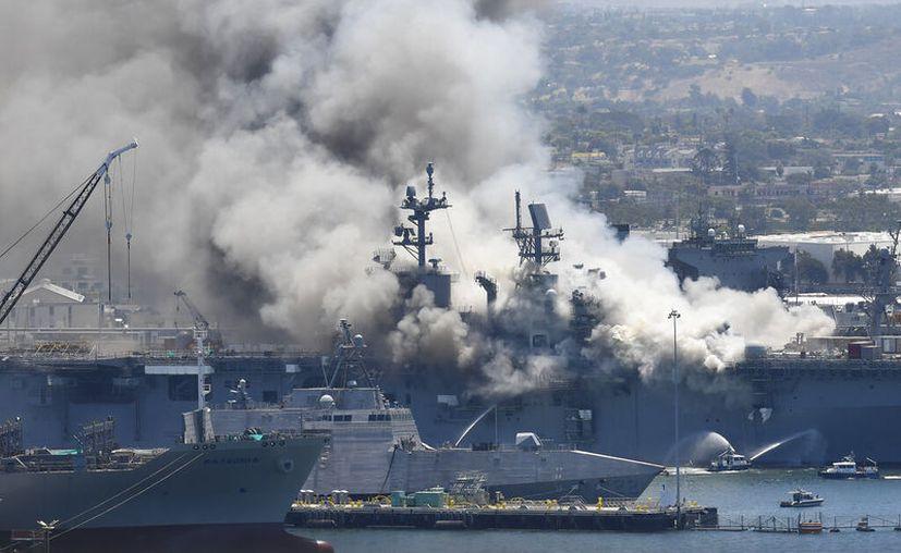 Una enorme columna de humo se eleva sobre el buque USS Bonhomme Richard en la base naval de San Diego, tras un incendio y explosión a bordo. (AP Foto/Denis Poroy)