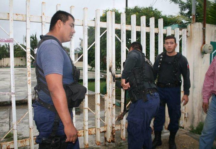 Los elementos policíacos utilizaron alicates y martillos para tratar de abrir las rejas. (Benjamín Pat/SIPSE)