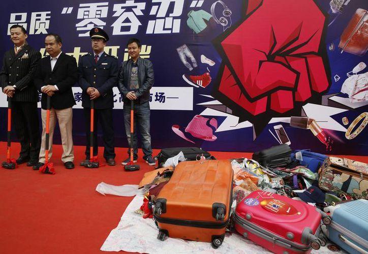 Comerciantes y funcionarios en un evento para combatir la falsificación de productos, afuera del mercado de Silk Street, en Beijing. (Agencias)