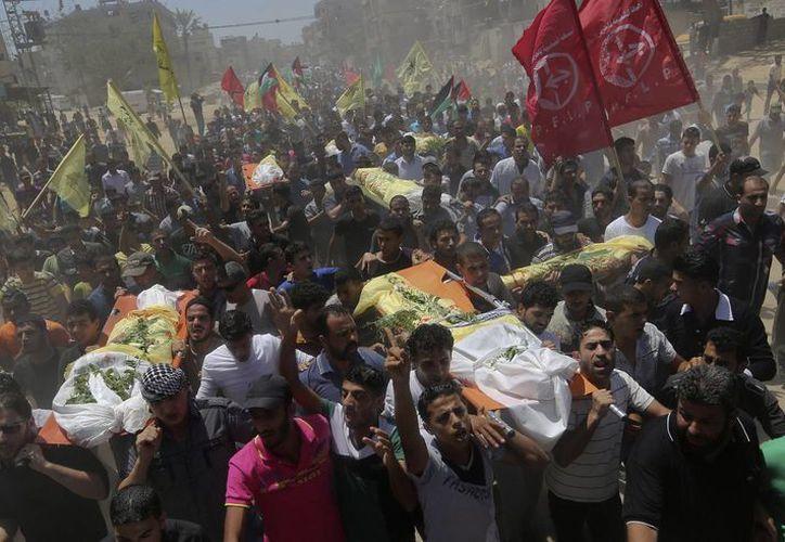Palestinos cargan los cuerpos de siete muertos este miércoles durante los ataques de Israel. El funeral se realiza en el campo de refugiados Khan Younis, en el sur de la Franja de Gaza. (Foto AP)