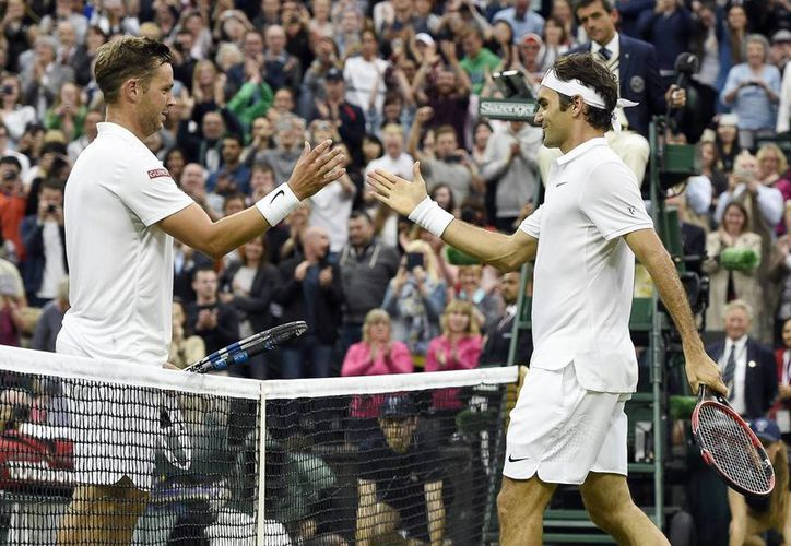 El tenista suizo Roger Federer (d) celebra su victoria en la segunda ronda dando la mano a su opositor británico Marcus Willis (i) durante el torneo de Wimbledon que se disputa en All England Lawn Tennis Club de Londres, Reino Unido. (EFE)