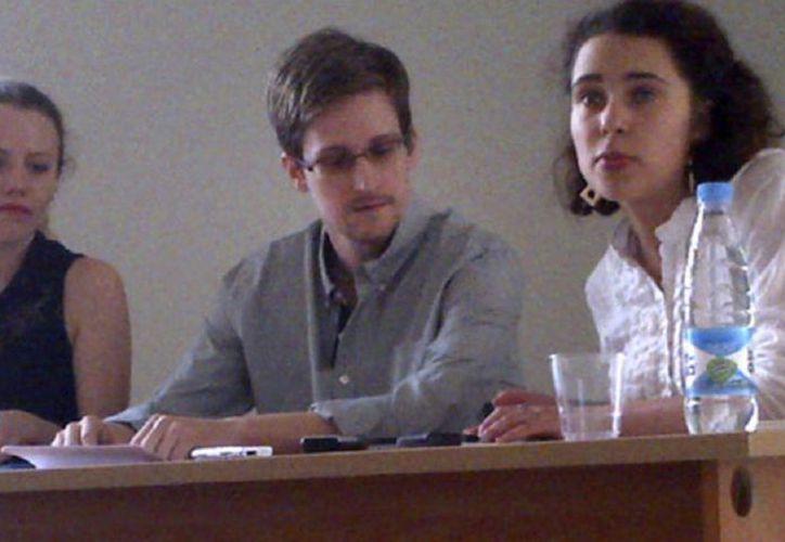 Abogados y activistas de Derechos Humanos acudieron este viernes a la cita convocada por Snowden (c) en la terminal del aeropuerto moscovita. (Agencias)