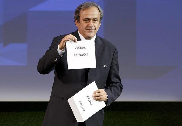 El presidente de la UEFA, Michel Platini, muestra la boleta donde se asienta que Londres será la sede de la final de la Eurocopa 2020. (AP)