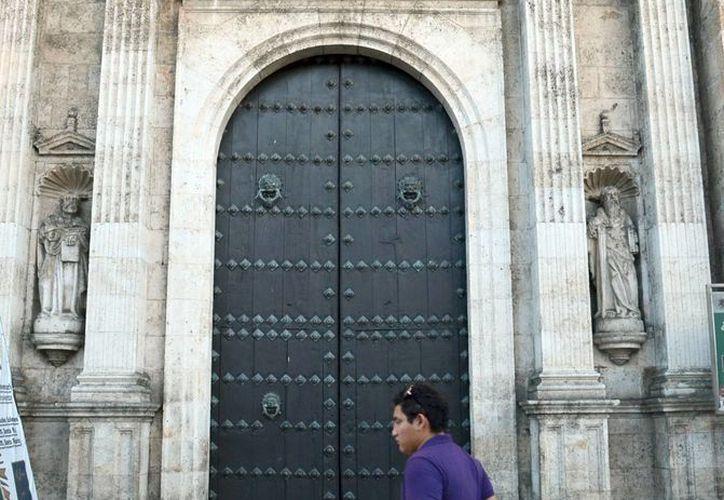 El domingo 13 será el último día para ganar una indulgencia con motivo del Año de la Misericordia. Imagen de una persona mientras camina en la puerta de la Catedral de Mérida. (Milenio Novedades)