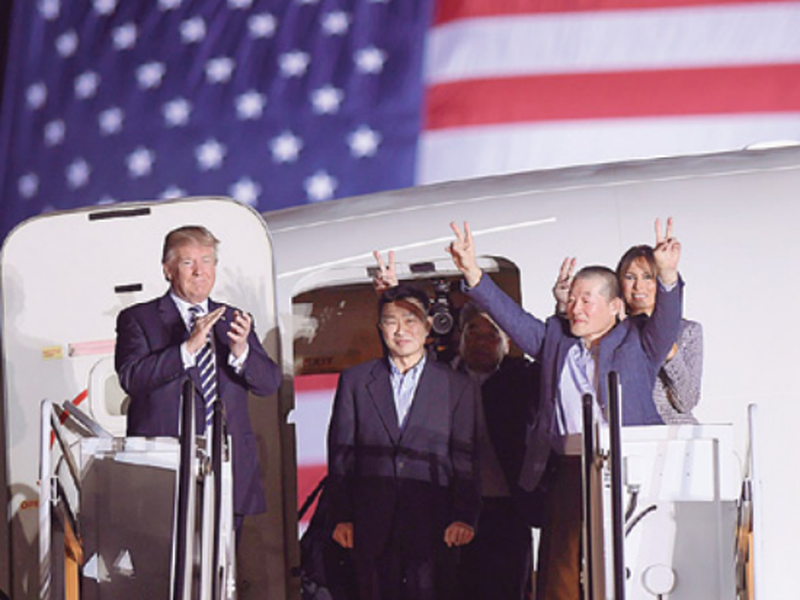 President Donald Trump, from left, greets Tony Kim, Kim Hak Song, seen in the shadow, and Kim Dong Chul, three Americans detained in North Korea for more than a year, as they arrive at Andrews Air Force Base in Md. (AP)