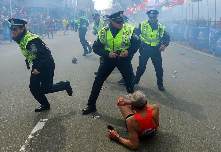 En esta fotografía del 15 de abril de 2013 se ve a Bill Iffrig, de 78 años, tirado en el piso mientras policías acuden al lugar tras la segunda explosión registrada en el Maratón de Boston. (Agencias)