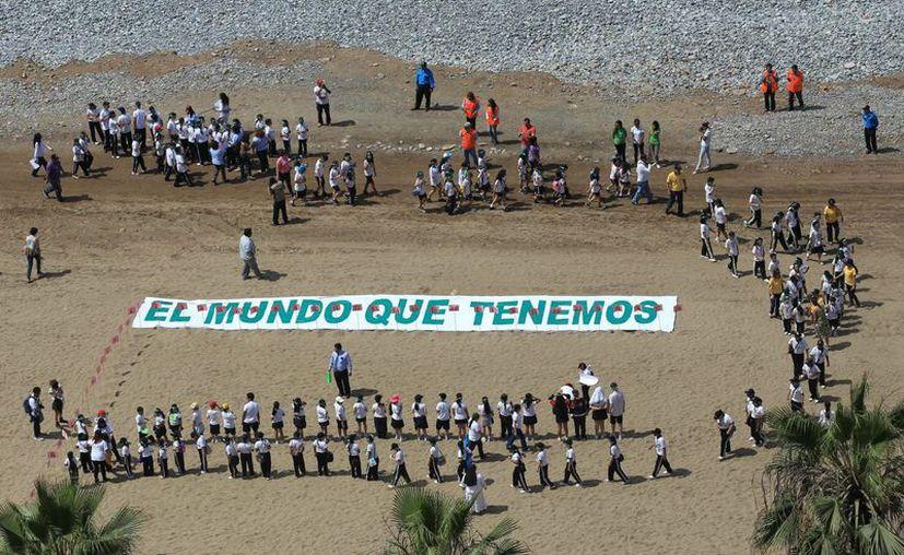"""Alrededor de 300 estudiantes, junto a sus maestros y padres, se preparan para formar la figura de un árbol junto a la frase """"El mundo que tenemos"""", en una playa del distrito limeño de Miraflores, para enviar un mensaje al mundo sobre el cuidado del planeta. (EFE)"""