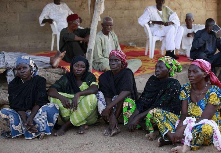 Madres de las menores secuestradas esperan noticias en las inmediaciones de Abuya, la capital del país. (AP)