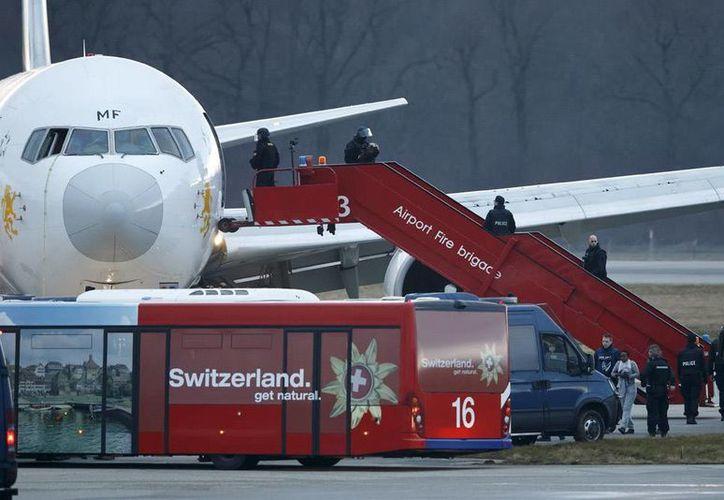 El copiloto de un vuelo de Ethiopian Airlines secuestró un avión, para pedir asilo político en Suiza. En la imagen, varios policías ayudan a los pasajeros a abandonar el aparato tras finalizar la emergencia, en el aeropuerto de Ginebra (Suiza) hoy. (EFE)