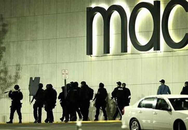 Agentes especiales y policías caminan fuera del centro comercial Garden State Plaza luego del tiroteo. (Agencias)
