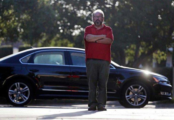 Bob Rand posa para una fotografía con su sedán Volkswagen Passat diésel, uno de los modelos cuyo software de emisiones contaminantes pudo haber sido manipulado. (Agencias)