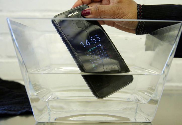 En esta fotografía de archivo de 2012, el Samsung Galaxy S7 Edge es sumergido en agua durante un preestreno de la tienda Samsung, la Samsung 837, en el Meatpacking District de Nueva York. (AP Foto/Richard Drew, Archivo)