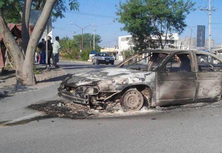Hombres armados y fuerzas federales se enfrentaron desde las primeras horas de este domingo en Reynosa, en Tamaulipas. Imagen de un vehículo incinerado a la salida a Monterrey. (Foto Reynosa Código Rojo)