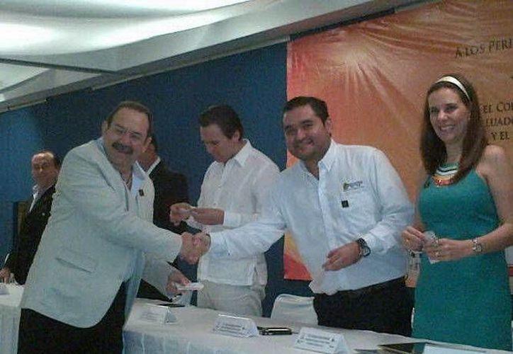 El secretario Mauricio Rodríguez Marrufo entrega su renovación de registro estatal al presidente del Colegio de Valuadores de Quintana Roo, Heyden José Cebada Ramírez. (Cortesía/SIPSE)