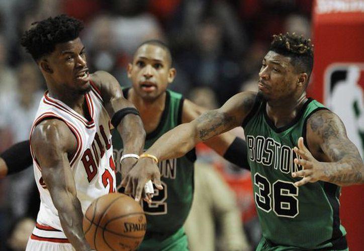 Jimmy Buttler (i), que en la foto enfrenta a Marcus Smart, tuvo un desempeño crucial para Bulls de Chicago en partido contra Celtics. (AP)