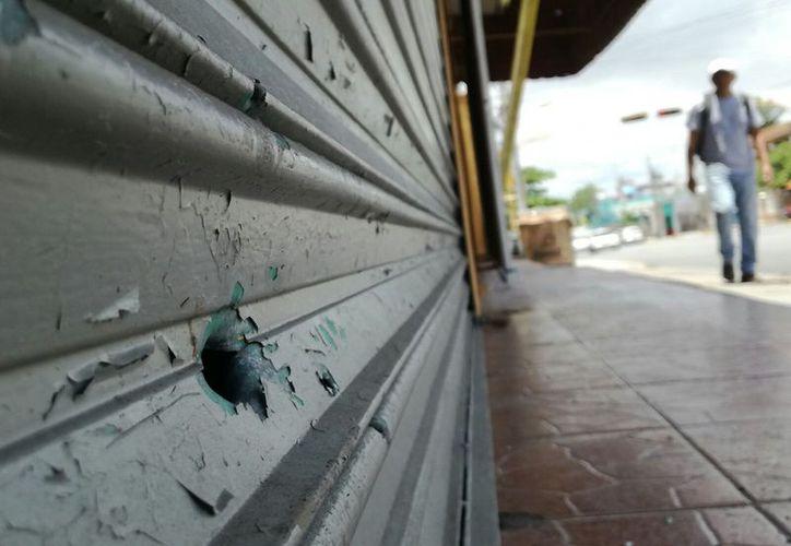 La cortina del bar registró un impacto de bala. (Eric Galindo/SIPSE)