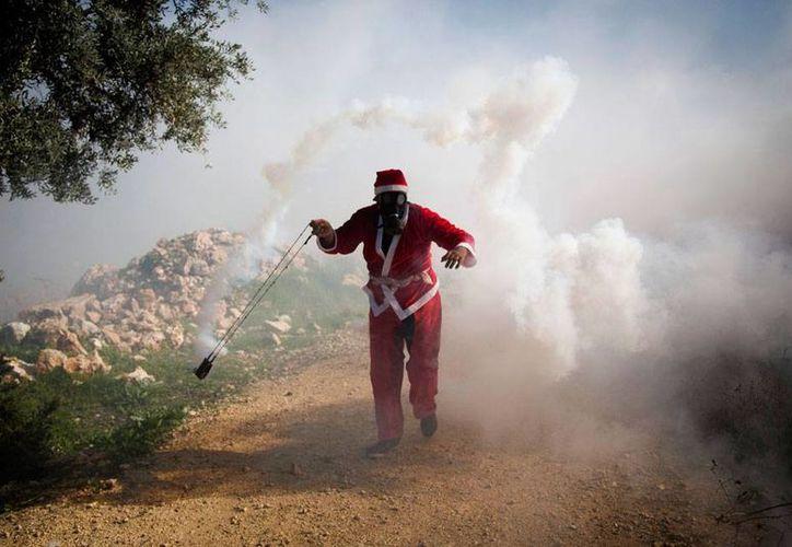 Un palestino atacó a dos policías de Israel. En la im imagen, otro palestino vestido de Santa Claus intenta alejar un gas lacrimógeno lanzado por fuerzas israelíes, durante una protesta de los palestinos por la añeja ocupación judía de territorios árabes. La imagen es de contexto.  (AP)
