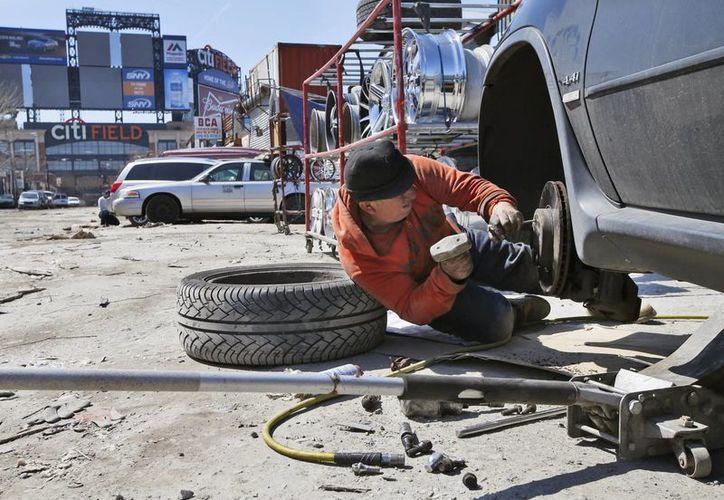 Un hombre repara un automóvil en una calle de tierra cerca del campo de los New York Mets en el barrio Willets Point, de Queens. (Agencias)