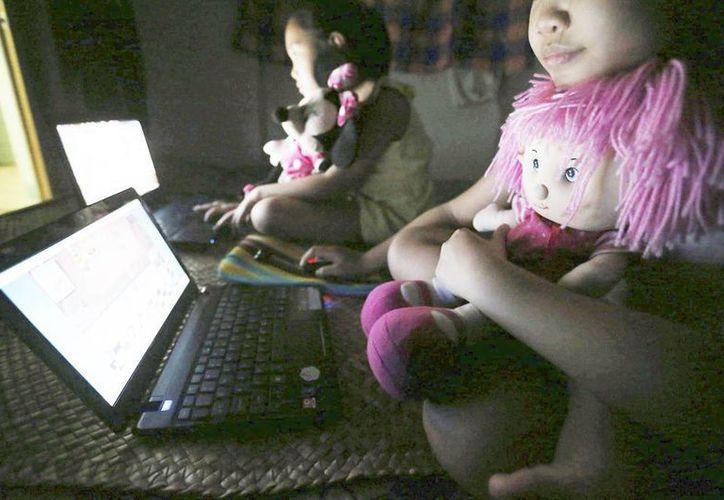 Niños juegan con sus computadoras en su casa en Quezon, Filipinas. La pobreza en este país hace que, a veces, las propias madres permitan la prostitución de sus hijos. (EFE/Archivo)