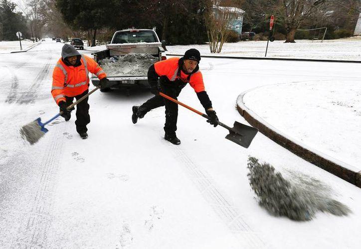 La tormenta invernal Pax ya cobró la vida de 14 persona en Estados Unidos, y ha trastocado la vida de más de 10 estados. En la imagen, trabajadores de los servicios públicos echan sal mezclada con arena en una calle cubirta de nieve en Avondale Estates, Georgia. (Efe)