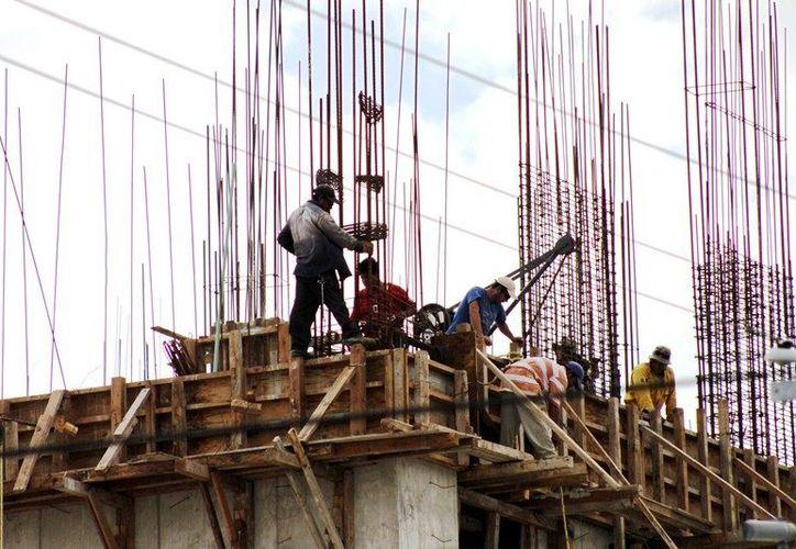 La construcción de un céntrico hotel en la ciudad, donde los albañiles trabajan a una altura considerable y sin usar equipamiento de ante la complacencia del supervisor de la obra.  (Francisco Sansores/SIPSE)