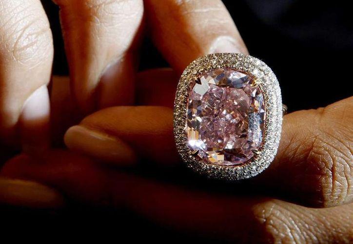 El diamante rosa intenso se encuentra incrustado en un anillo y rodeado de una doble hilera de pequeñas gemas blancas y tuvo un costo de 28.7 millones de francos suizos. (EFE)