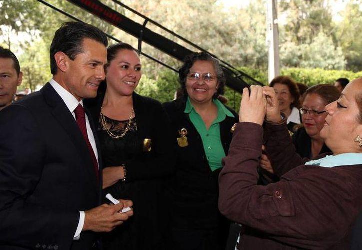 Las madres que acudieron a la ceremonia oficial  de la celebración de su día, en Los Pinos, aprovecharon para tomarle, de cerca, fotos al presidente Enrique Peña Nieto. (NTX)