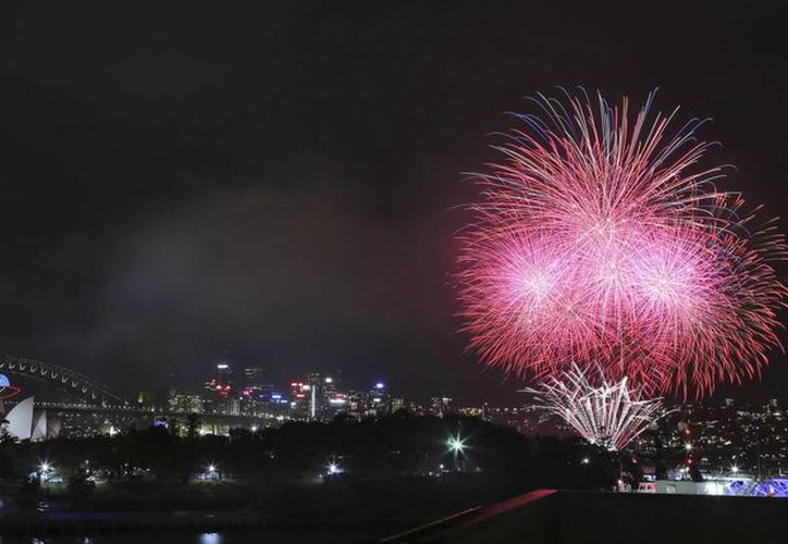 Fuegos artificiales estallan cerca del puente Harbor y la Ópera durante las celebraciones de Año Nuevo en Sydney, Australia. (Agencias)