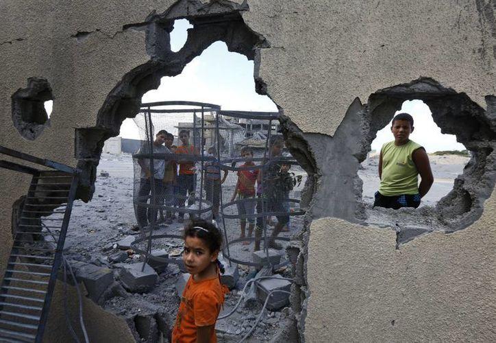 Una niña palestina se detiene junto a una casa destruida una noche anterior por un misil israelí en Rafah, sur de la Franja de Gaza. (Agencias)