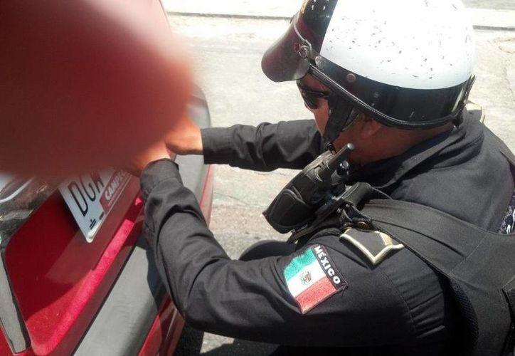 Momento en que el policía retira la placa al automóvil del conductor que lo denuncia. (Cortesía)