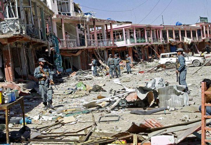 Fuerzas de seguridad afganas observan los destrozos que dejaron las explosiones perpetradas por el Talibán en Gasni, Afganistán. (Agencias)