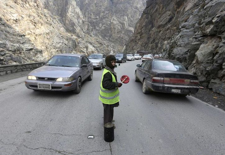 Sedaqat hace señas a vehículos en el paso de Maipur, en la principal autopista de Kabul a Pakistán, cerca de Kabul. (AP/Rahmat Gul)