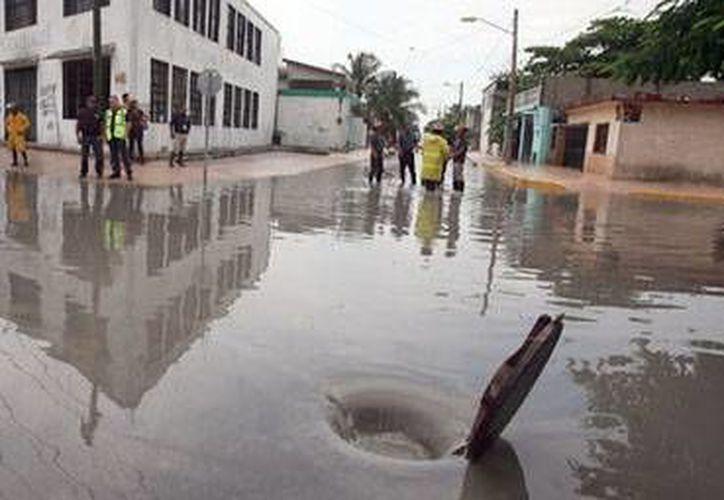 La avenida Bonampak presentó inundaciones:  bomberos y trabajadores de Protección Civil y Servicios Públicos realizaron trabajos para que fluyera el agua. (Redacción/SIPSE)