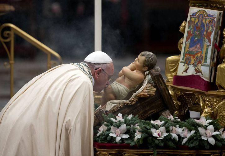 El Papa Francisco besa a una imagen del Niño Dios al arribar a la Basílica de San pedro para celebrar las vísperas de Año Nuevo, este 31 de diciembre de 2014. (Foto. AP)