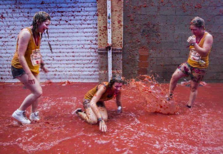 Tres jovenes participan en la fiesta de la Tomatina. (EFE)