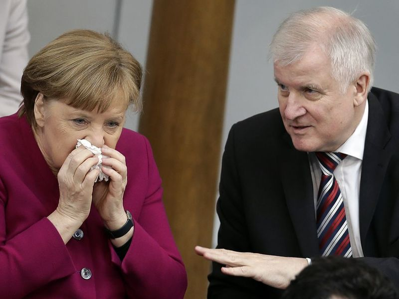 German Chancellor Angela Merkel, left, and German Interior Minister Horst Seehofer, right, talk during a meeting of the German federal parliament, Bundestag, in Berlin.