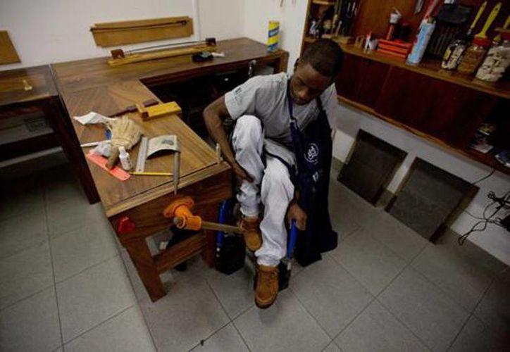 Juan Carlos Marrón se acomoda para comenzar a trabajar en la reparación de instrumentos en un taller para discapacitados. (Agencias)