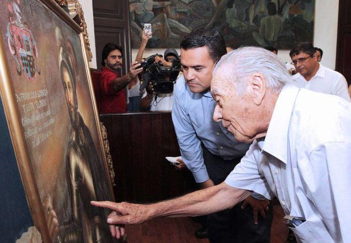 El pintor Ermilo Torre Gamboa muestra las huellas del paso del tiempo en el retrato del conquistador Francisco de Montejo El Mozo, que adorna el Salón del Cabildo en Mérida. (Cortesía)