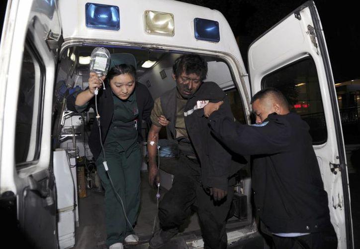 Foto proporcionada por la Agencia de Noticias Xinhua de China, se muestra a un minero herido, que es transferido a un hospital después del derrumbe. (Agencias)