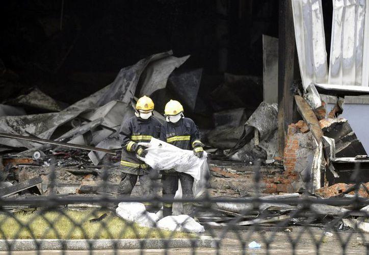 Bomberos preparan bolsas para meter cadáveres, a las afueras de la planta avícola. (Agencias)