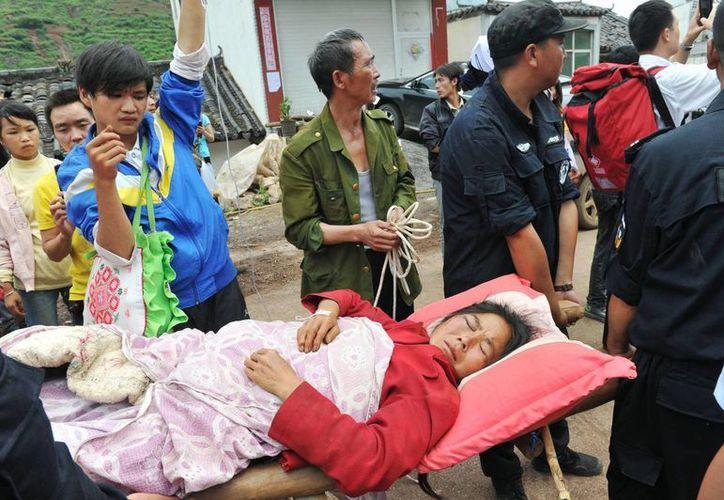 Una mujer es rescatada de entre los escombros en el condado de Ludian de Zhaotong, ciudad de la provincia suroccidental china de Yunnan. (Agencias)